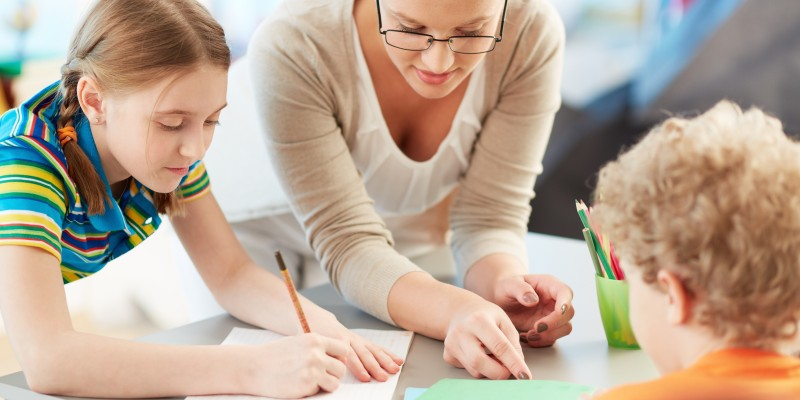 Portrait of diligent schoolgirl drawing at lesson surrounded by her classmate and teacher